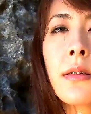 Ярко азиатское фея рика кавамура позирует на камне на берегу моря